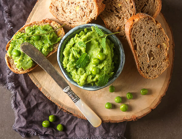 Minted pea and soya bean hummus in a bowl on a chopping board with bread