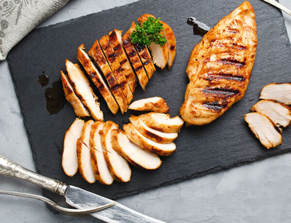 Grilled chicken breasts sliced on a black chopping board