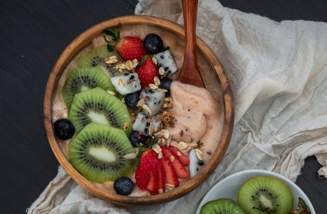 Bowl of smoothie topped with fresh fruit